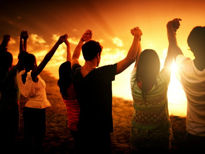 People holding hands in the air around a bonfire doing group therapy