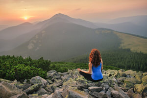Woman feels freedom and enjoys the beautiful view in the mountains and looking on sunset